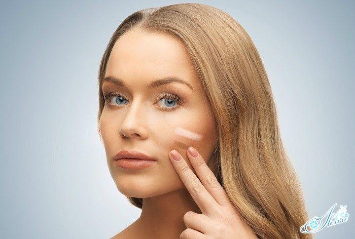 Нанесение девушкой тонального крема на лицо