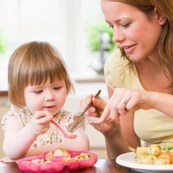 Мама и ребенок учатся есть ложкой за обедом