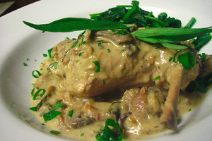 Мясо кролика с грибами и сметаной на тарелке