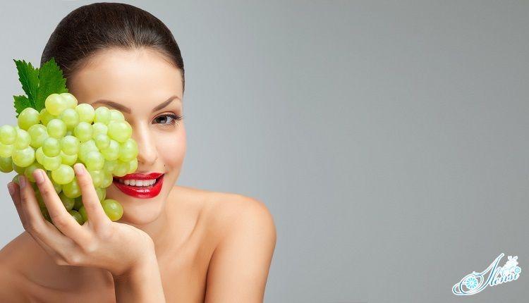 девушка держит гроздь винограда