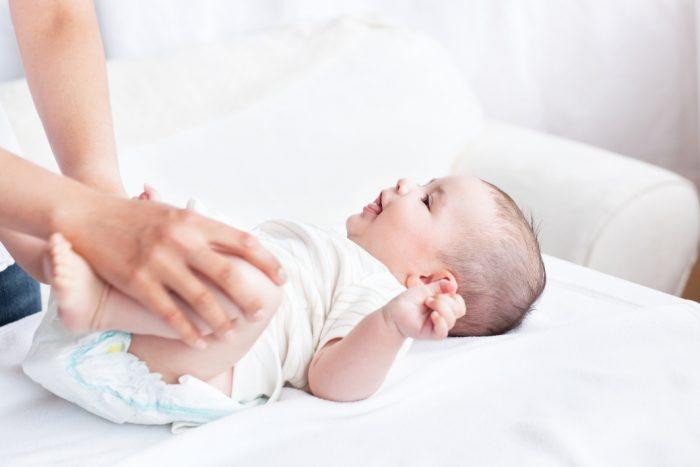 Мама меняет подгузники малышу на столике