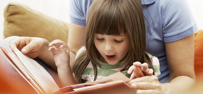 Девочка читает книгу с мамой на диване