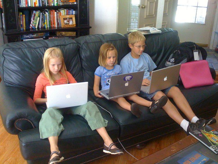 Дети играют в игры на ноутбуках на диване